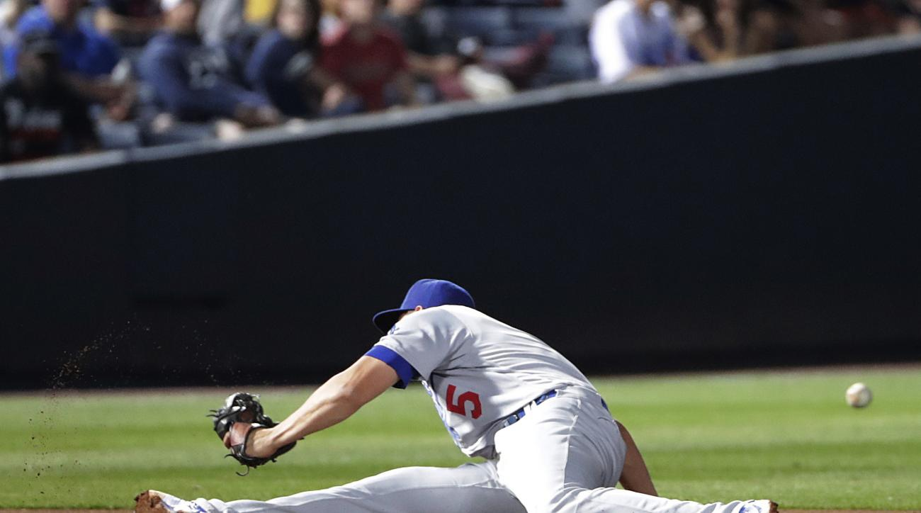 Los Angeles Dodgers shortstop Corey Seager commits a fielding error, allowing Atlanta Braves' Adonis Garcia to reach first base during the fourth inning of a baseball game Tuesday, April 19, 2016, in Atlanta. (AP Photo/David Goldman)