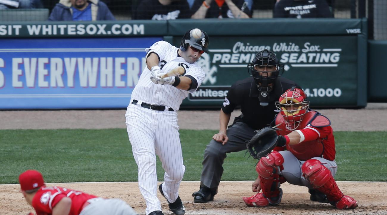 Chicago White Sox's Alex Avila, left, doubles off Los Angeles Angels starting pitcher Garrett Richards as catcher Geovany Soto and umpire Gabe Morales watch during the fifth inning of a baseball game Wednesday, April 20, 2016, in Chicago. (AP Photo/Charle