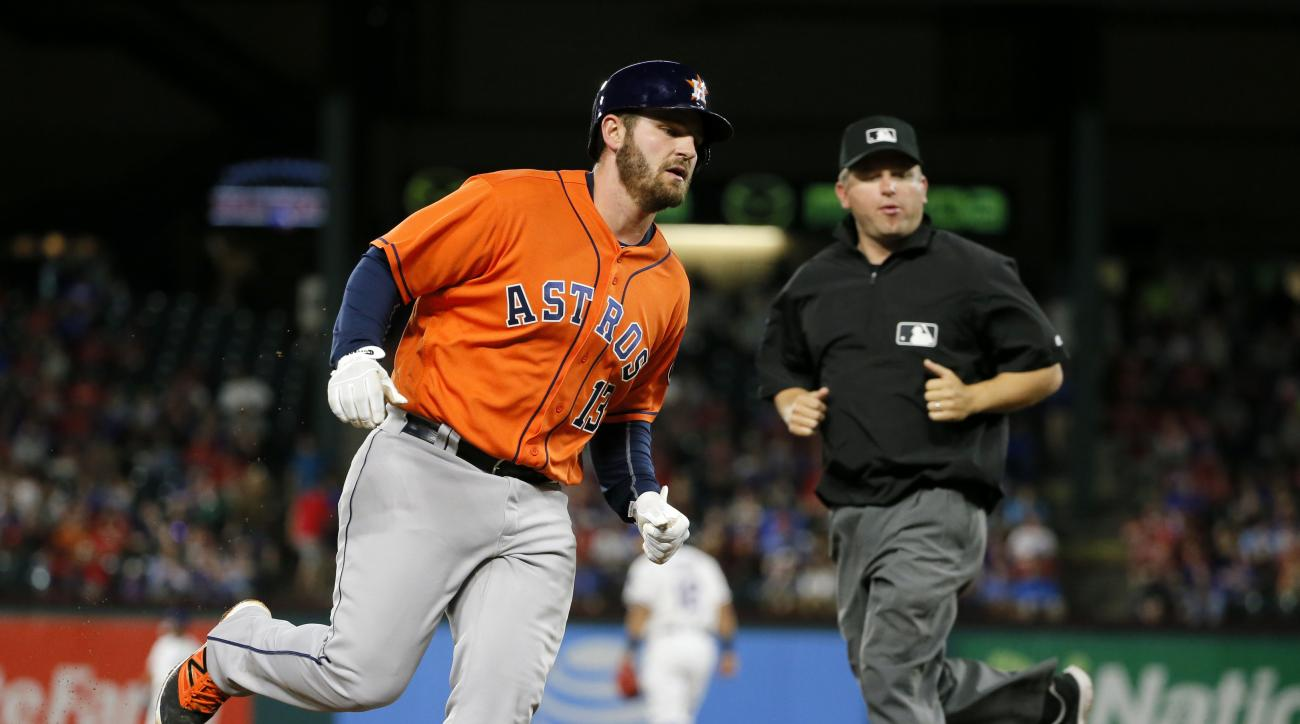 Houston Astros' Tyler White rounds third as base umpire Clint Fagan, right, watches White trot home following his solo home run that came off a pitch from Texas Rangers starting pitcher Cole Hamels in the sixth inning of a baseball game, Wednesday, April