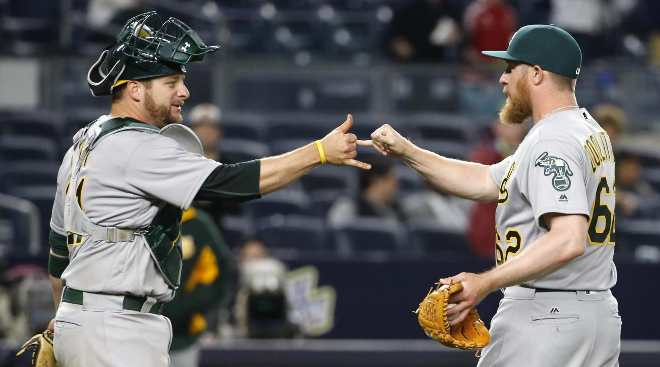 Oakland Athletics catcher Stephen Vogt congratulates relief pitcher Sean Doolittle (62) after Doolittle closed out the Athletics' 5-2 victory over the New York Yankees in a baseball game in New York, Wednesday, April 20, 2016. (AP Photo/Kathy Willens)