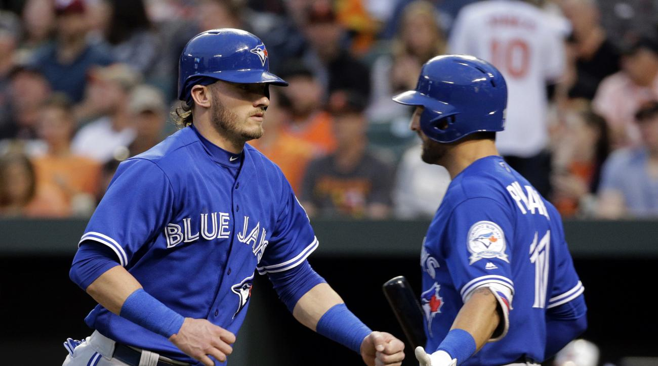 Toronto Blue Jays' Josh Donaldson, left, fist bumps teammate Kevin Pillar after scoring on a bases-loaded walk to Justin Smoak in the first inning of a baseball game in Baltimore, Thursday, April 21, 2016. (AP Photo/Patrick Semansky)
