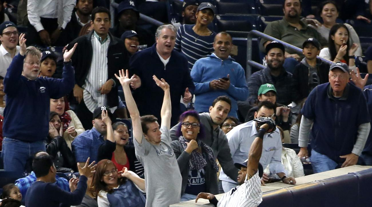 Fans react after New York Yankees left fielder Aaron Hicks, who has the ball in his glove, leaped to catch Chris Coughlan's fourth-inning foul ball in a baseball game in New York, Thursday, April 21, 2016. (AP Photo/Kathy Willens)