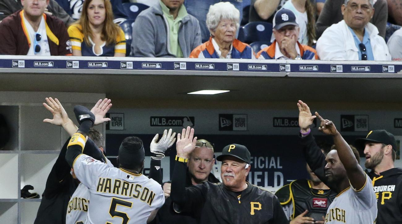 Pittsburgh Pirates' Josh Harrison is congratulated at the dugout after he drove in his second run with a single, then stole second, took third on a passed ball, and scored on a wild pitch during the fourth inning of a baseball game against the San Diego P