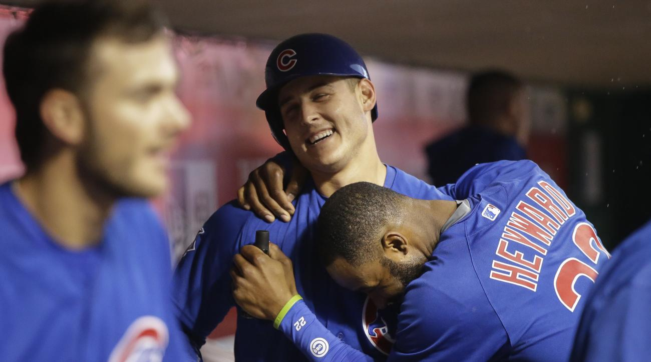 Chicago Cubs' Anthony Rizzo, center, celebrates in the dugout with Jason Heyward (22) after hitting a solo home run off Cincinnati Reds starting pitcher Jon Moscot during the fourth inning of a baseball game, Friday, April 22, 2016, in Cincinnati. (AP Pho