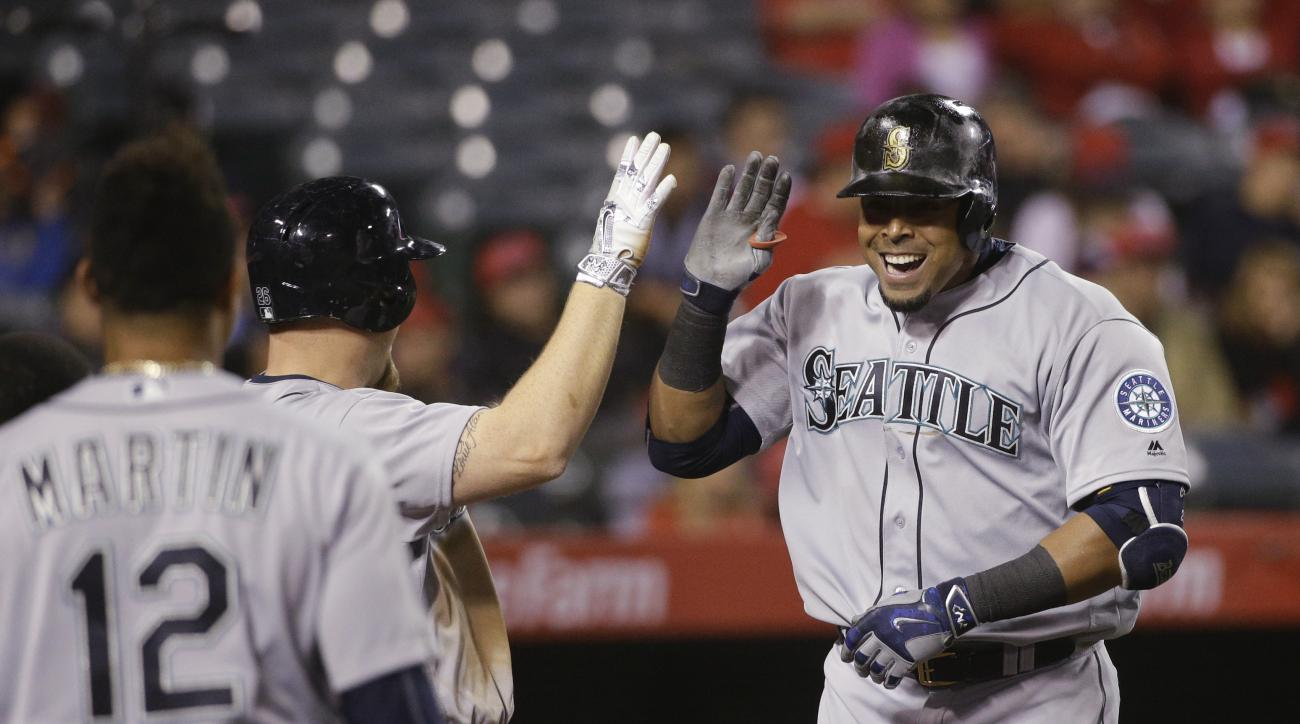Seattle Mariners' Nelson Cruz, right, celebrates his two-run home run with Adam Lind during the 10th inning of a baseball game against the Los Angeles Angels, Friday, April 22, 2016, in Anaheim, Calif. (AP Photo/Jae C. Hong)