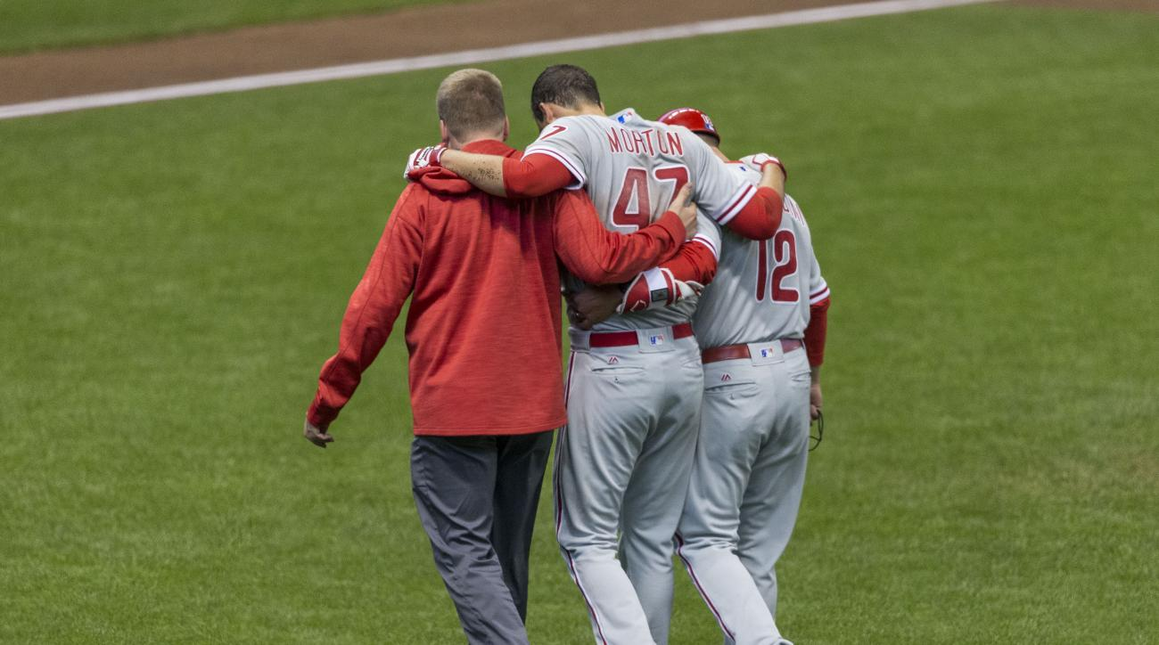 Philadelphia Phillies' Charlie Morton, center, is helped off the field after injuring his leg during the second inning of a baseball game against the Milwaukee Brewers, Saturday, April 23, 2016, in Milwaukee. (AP Photo/Tom Lynn)