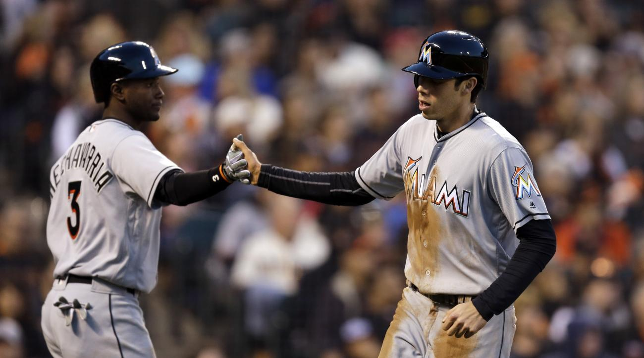 Miami Marlins' Christian Yelich, right, is congratulated by Adeiny Hechavarria (3) after scoring against the San Francisco Giants during the sixth inning of a baseball game Saturday, April 23, 2016, in San Francisco. AP Photo/Ben Margot)