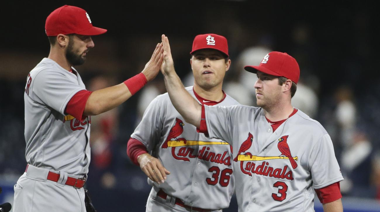St. Louis Cardinals' Jedd Gyorko high-fives with Matt Carpenter as they and Aledmys Diaz, center, leave the field following the Cardinals' 11-2 victory over the San Diego Padres in a baseball game Saturday, April 23, 2016, in San Diego. (AP Photo/Lenny Ig