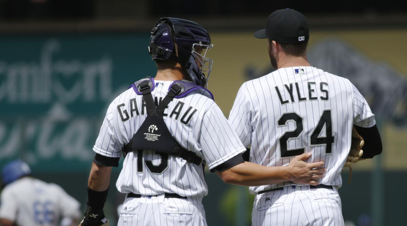 Colorado Rockies catcher Dustin Garneau, front left, confers with starting pitcher Jordan Lyles after Lyles walked Los Angeles Dodgers' Adrian Gonzalez in the first inning of a baseball game Sunday, April 24, 2016, in Denver. (AP Photo/David Zalubowski)