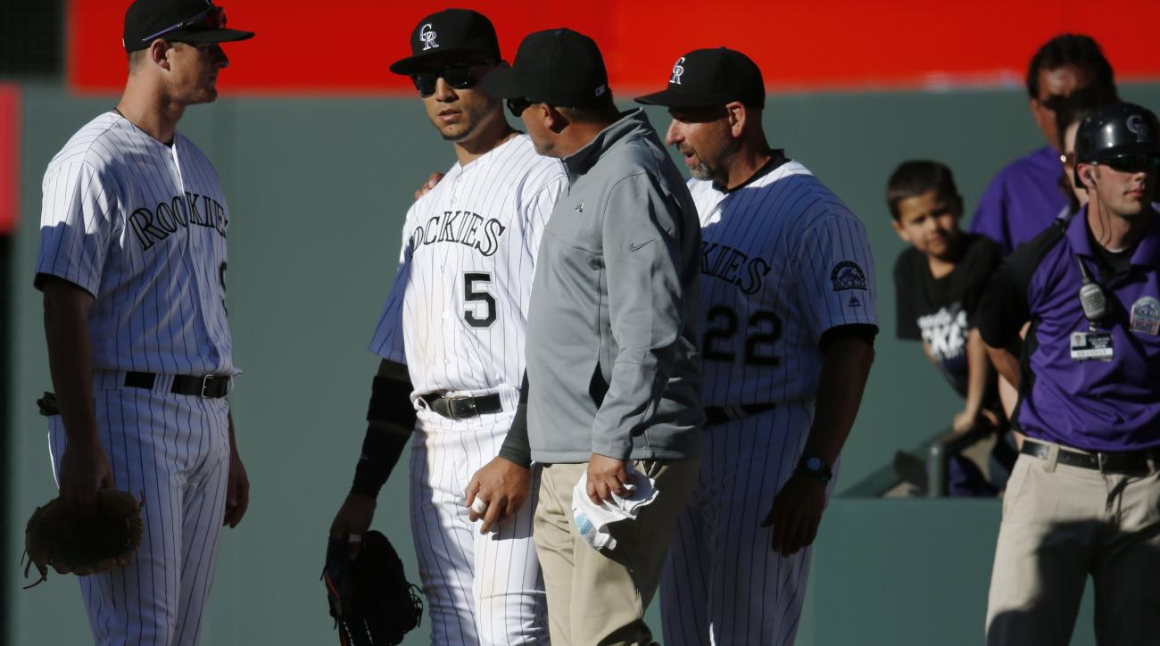 Colorado Rockies right fielder Carlos Gonzalez, second from left, is checked by athletic trainer Keith Dugger, third from left, as manager Walt Weiss, right, looks on after Gonzalez dived into the stands to try and catch a foul ball hit by Los Angeles Dod