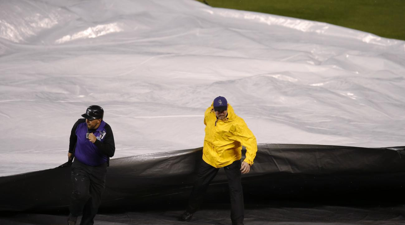 Field guards pull the tarpaulin over the infield as a heavy rain sweeps over Coors Field and prompts a delay in play in the bottom of the second inning of a baseball game between the Colorado Rockies and the Pittsburgh Pirates on Monday, April 25, 2016, i