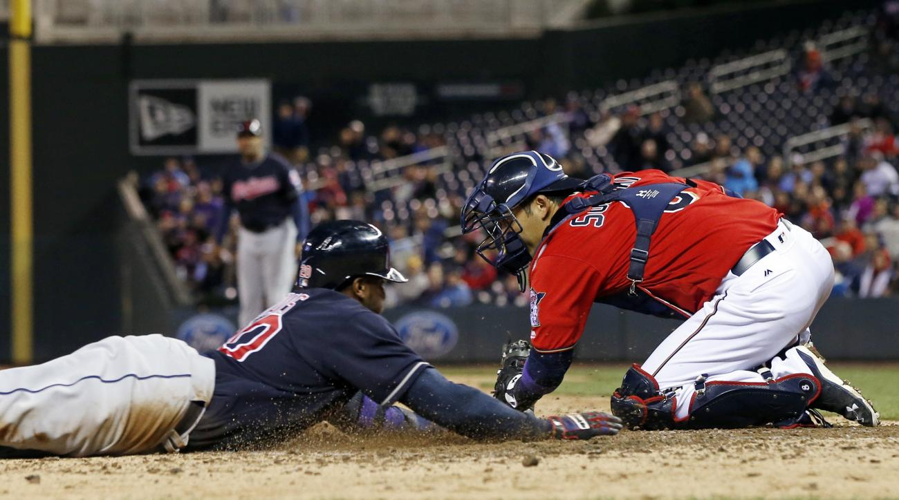 Cleveland Indians' Rajai Davis, left, slides safely into home to score on a Jason Kipnis single as Minnesota Twins catcher Kurt Suzuki makes the tag minus the ball in the fifth inning of a baseball game Monday, April 25, 2016, in Minneapolis. (AP Photo/Ji