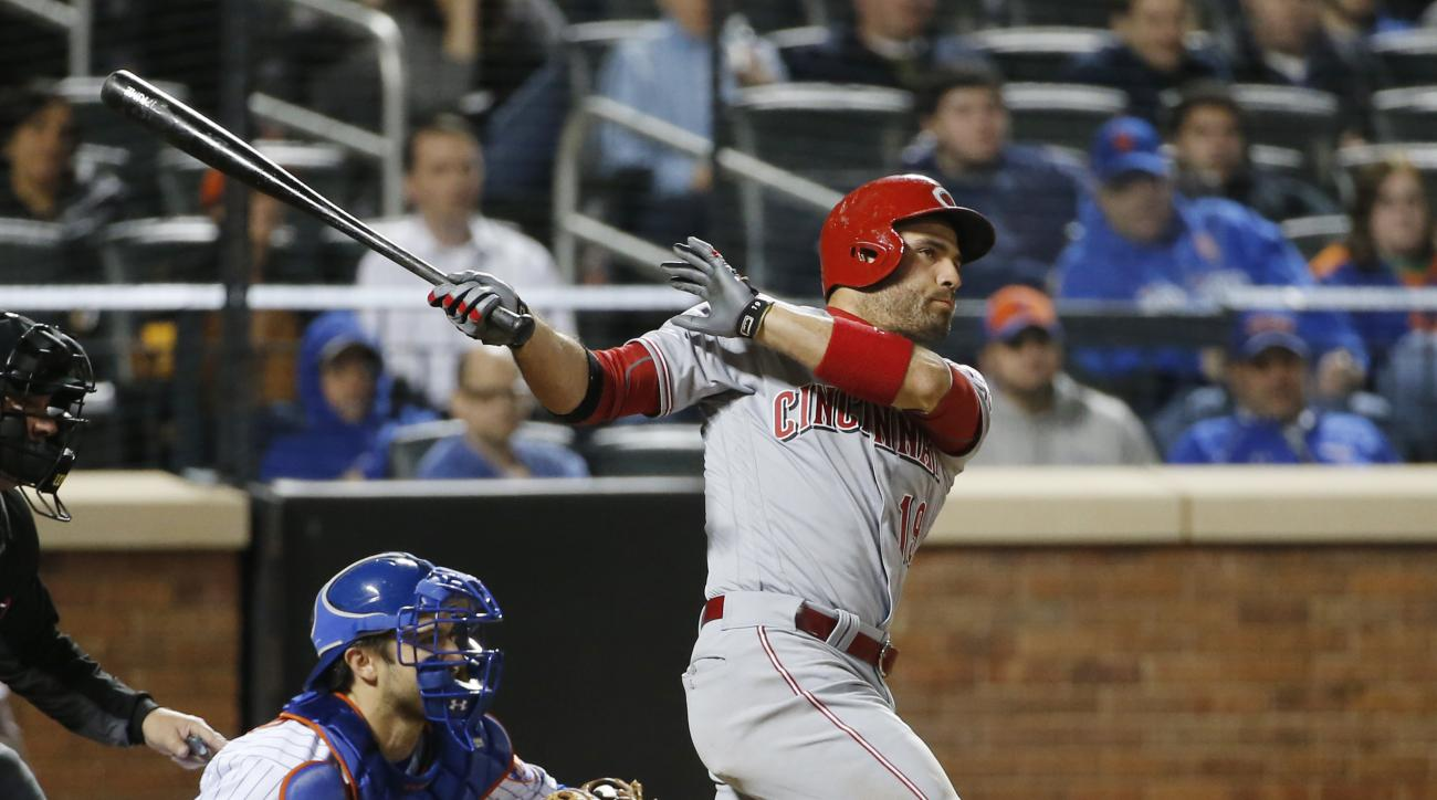 New York Mets catcher Travis d'Arnaud, left, watches as Cincinnati Reds Joey Votto (19) hits a game-tying, seventh-inning, RBI single in a baseball game Monday, April 25, 2016, in New York. (AP Photo/Kathy Willens)