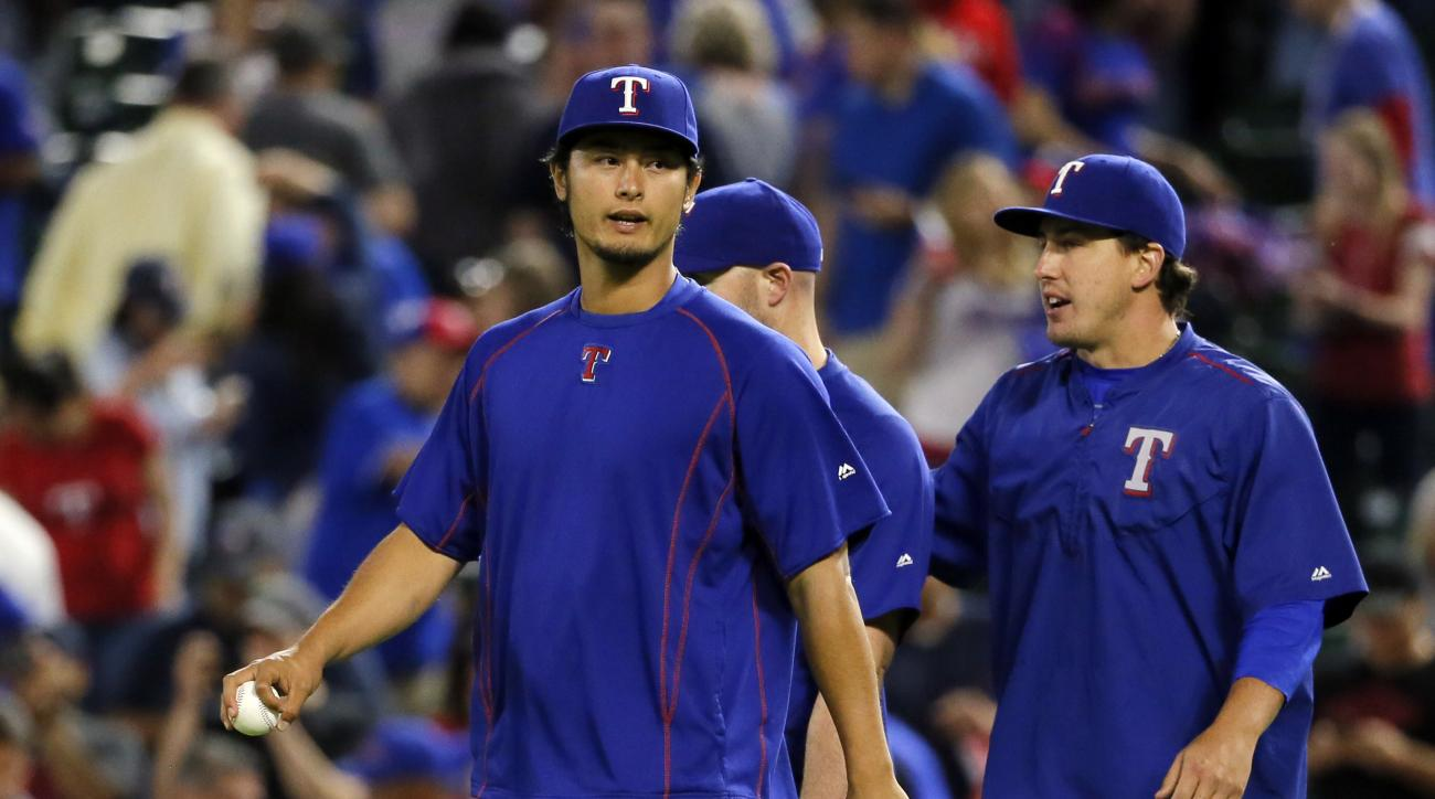 Texas Rangers' Yu Darvish of Japan and Derek Holland, right, walk on to the field to celebrate their 6-3 win over the Baltimore Orioles in a baseball game,  Thursday, April 14, 2016, in Arlington, Texas. (AP Photo/Tony Gutierrez)