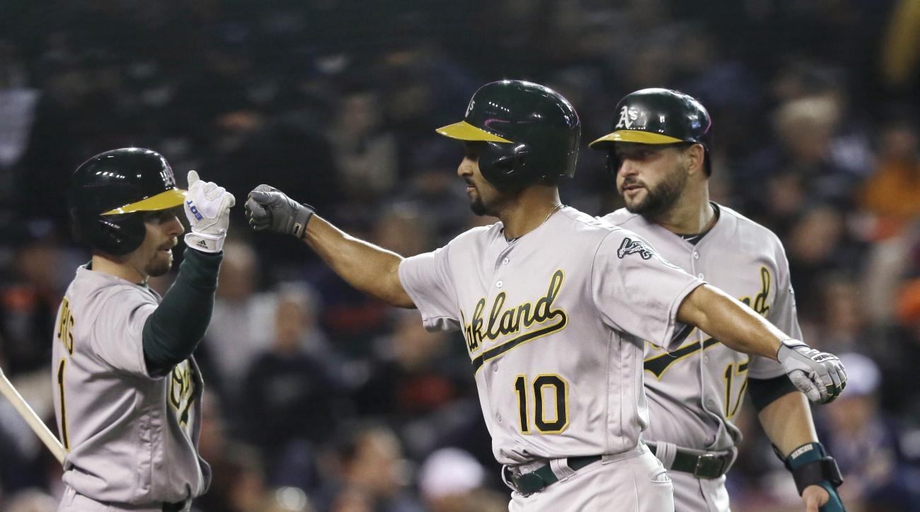 Oakland Athletics' Marcus Semien (10) meets Yonder Alonso, right, and Billy Burns at home plate after Seimein's two-run home run during the seventh inning of a baseball game against the Detroit Tigers, Tuesday, April 26, 2016, in Detroit. (AP Photo/Carlos