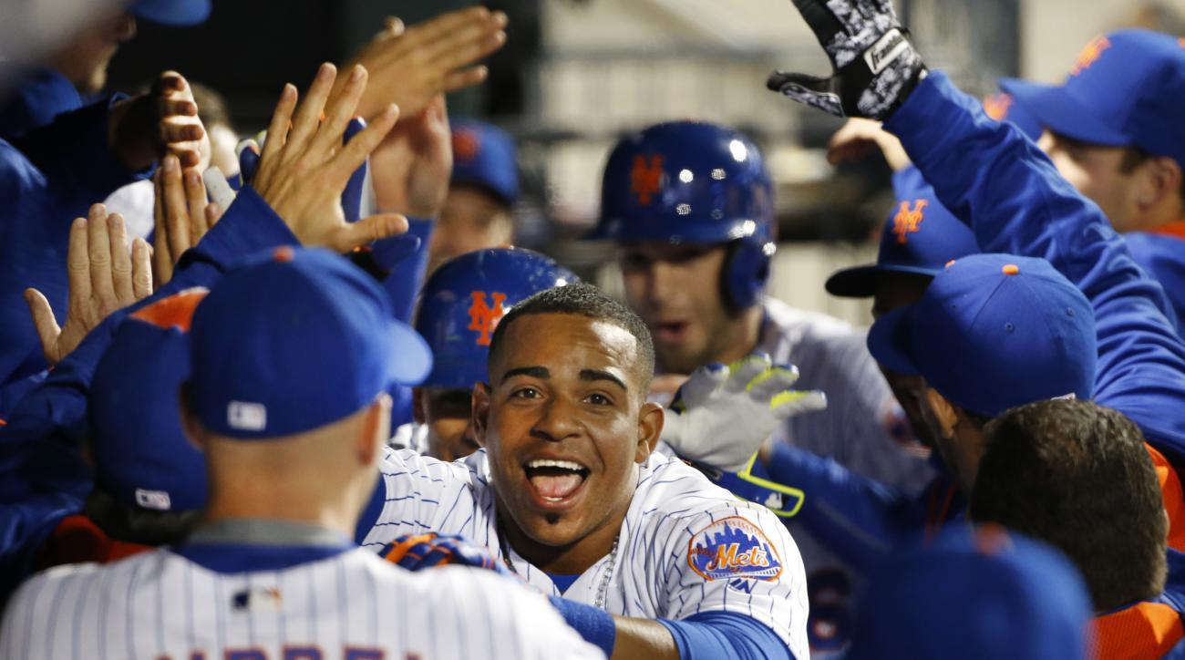 New York Mets Yoenis Cespedes, center, celebrates with teammates in the dugout after hitting a seventh-inning home run in a baseball game against the Cincinnati Reds, Tuesday, April 26, 2016, in New York. (AP Photo/Kathy Willens)