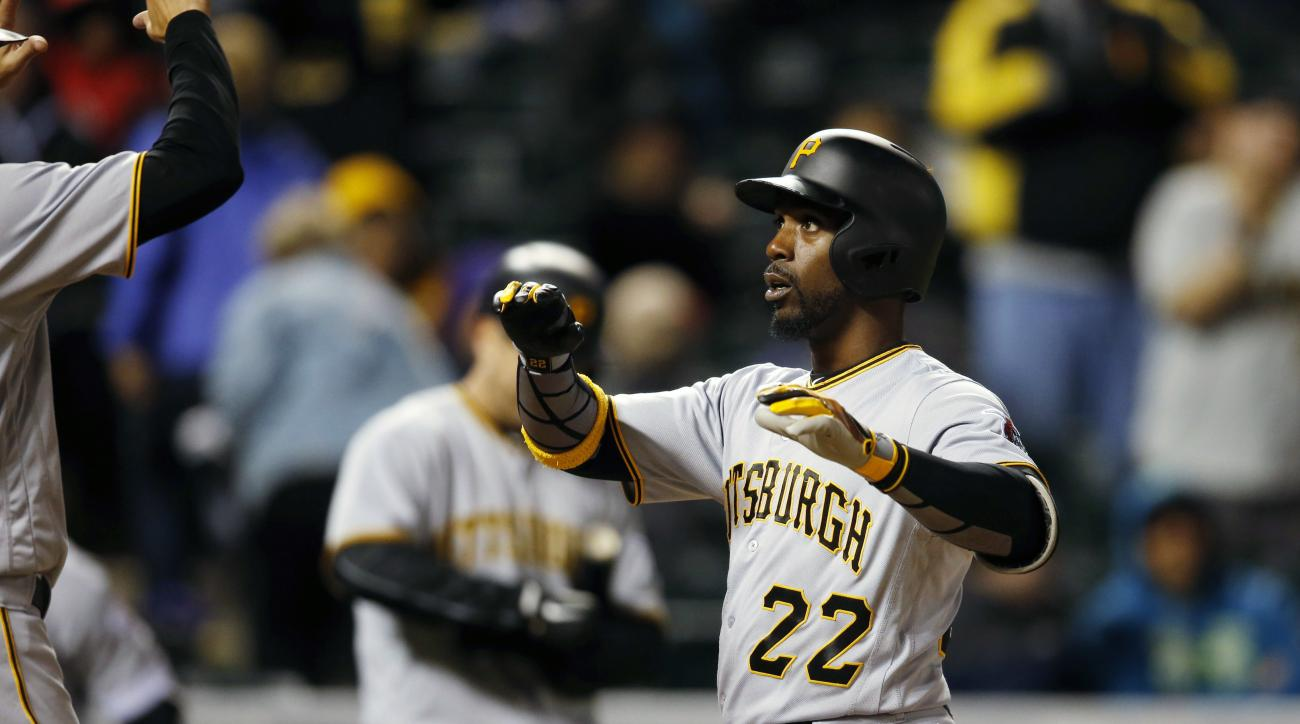 Pittsburgh Pirates' Andrew McCutchen raises his arms to celebrate as he crosses home plate after hitting a three-run home run off Colorado Rockies relief pitcher Christian Bergman in the sixth inning of a baseball game Tuesday, April 26, 2016, in Denver.