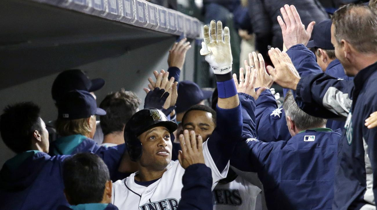 Seattle Mariners' Robinson Cano is congratulated in the dugout after his grand slam against the Houston Astros during the seventh inning of a baseball game Tuesday, April 26, 2016, in Seattle. (AP Photo/Elaine Thompson)