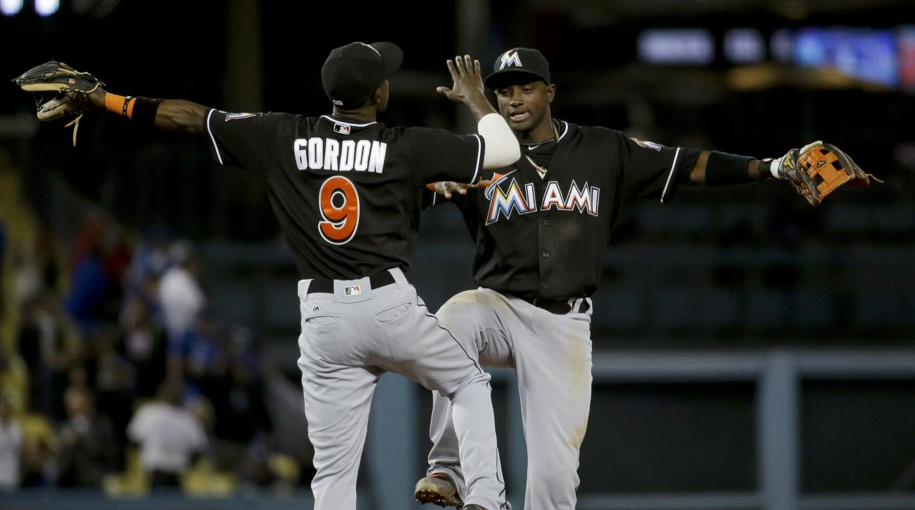 Miami Marlins second baseman Dee Gordon, left, and shortstop Adeiny Hechavarria celebrate after the Marlins' 6-3 win over the Los Angeles Dodgers in a baseball game in Los Angeles, Tuesday, April 26, 2016. (AP Photo/Chris Carlson)
