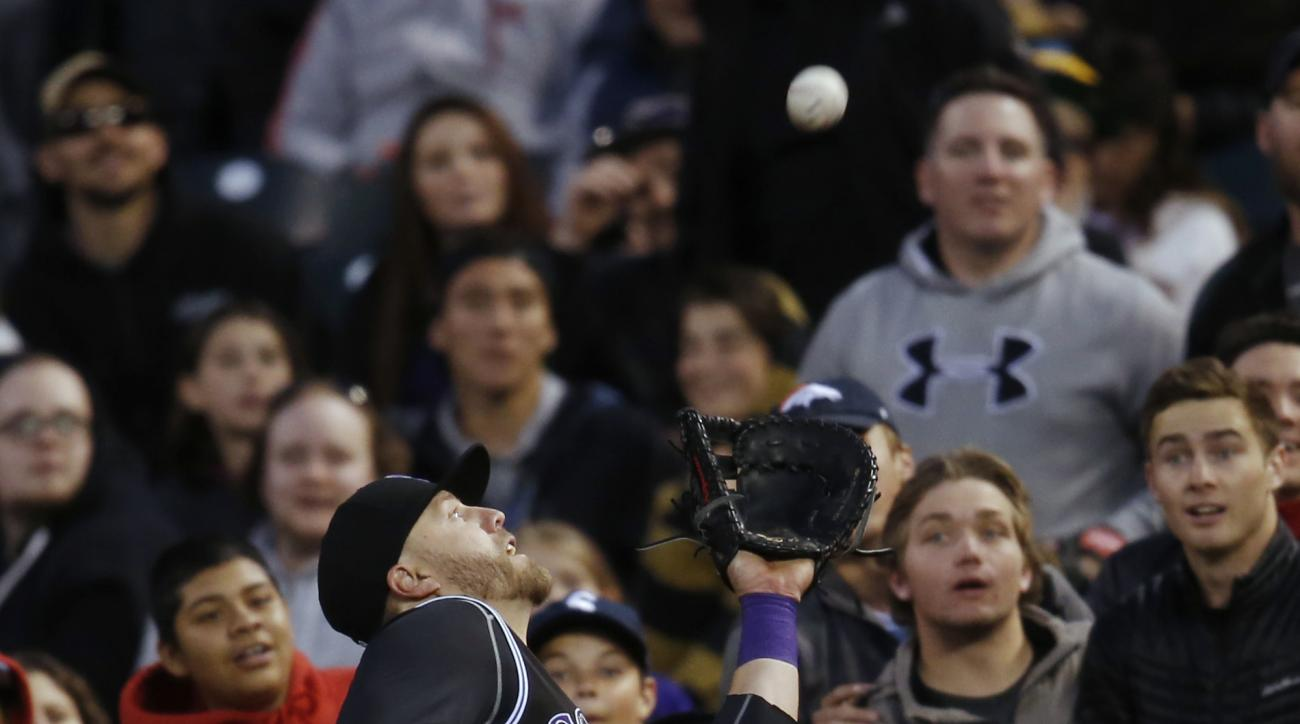 Colorado Rockies first baseman Mark Reynolds pulls in a pop foul by Pittsburgh Pirates' Jordy Mercer to end the top of the third inning of a baseball game Wednesday, April 27, 2016, in Denver. (AP Photo/David Zalubowski)