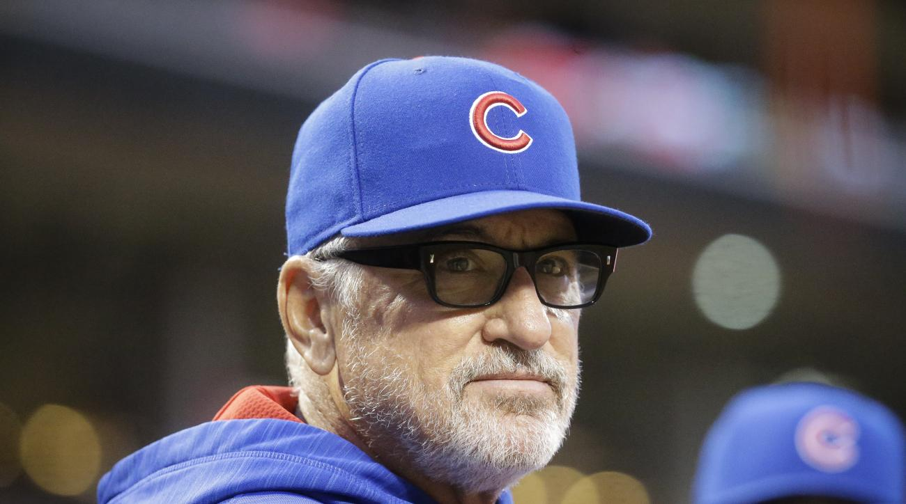 FILE - In this April 21, 2016 file photo, Chicago Cubs manager Joe Maddon stands in the dugout during a baseball game against the Cincinnati Reds in Cincinnati. Expectations for both Chicago baseball teams this year are high as the Cubs and White Sox lead