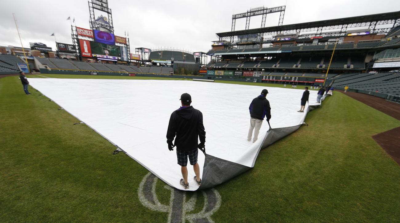 Members of the grounds crew at Coors Field adjust the tarpaulin on the diamond after the baseball game scheduled between the Colorado Rockies and Pittsburgh Pirates was cancelled because of inclement weather Thursday, April 28, 2016, in Denver. (AP Photo/