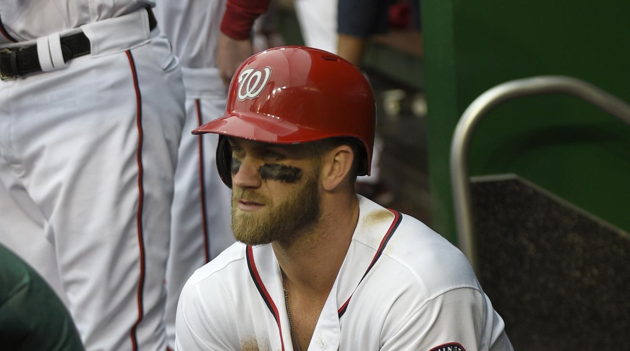 Washington Nationals' Bryce Harper warms his hands by a heater during the sixth inning of a baseball game against the Philadelphia Phillies, Thursday, April 28, 2016, in Washington. The Phillies won 3-0.(AP Photo/Nick Wass)