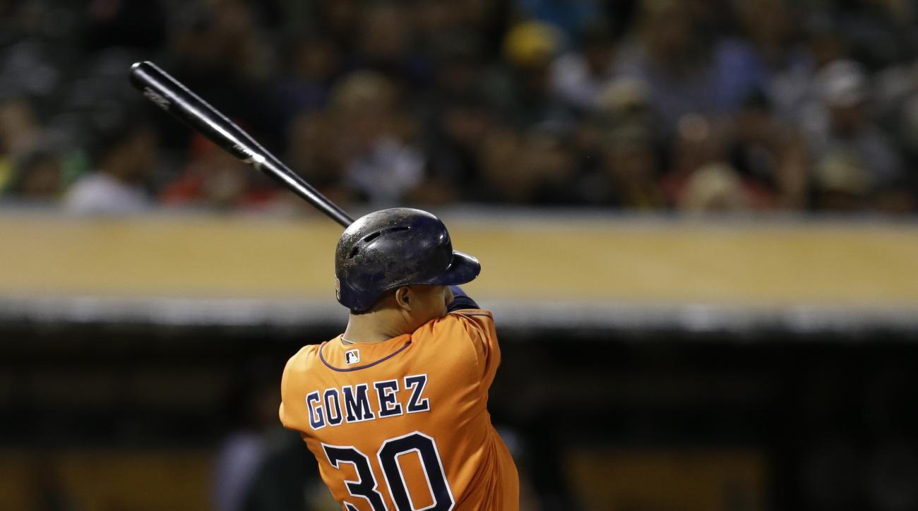 Houston Astros' Carlos Gomez swings for an RBI ground-rule double off Oakland Athletics' Sean Doolittle during the sixth inning of a baseball game Friday, April 29, 2016, in Oakland, Calif. (AP Photo/Ben Margot)