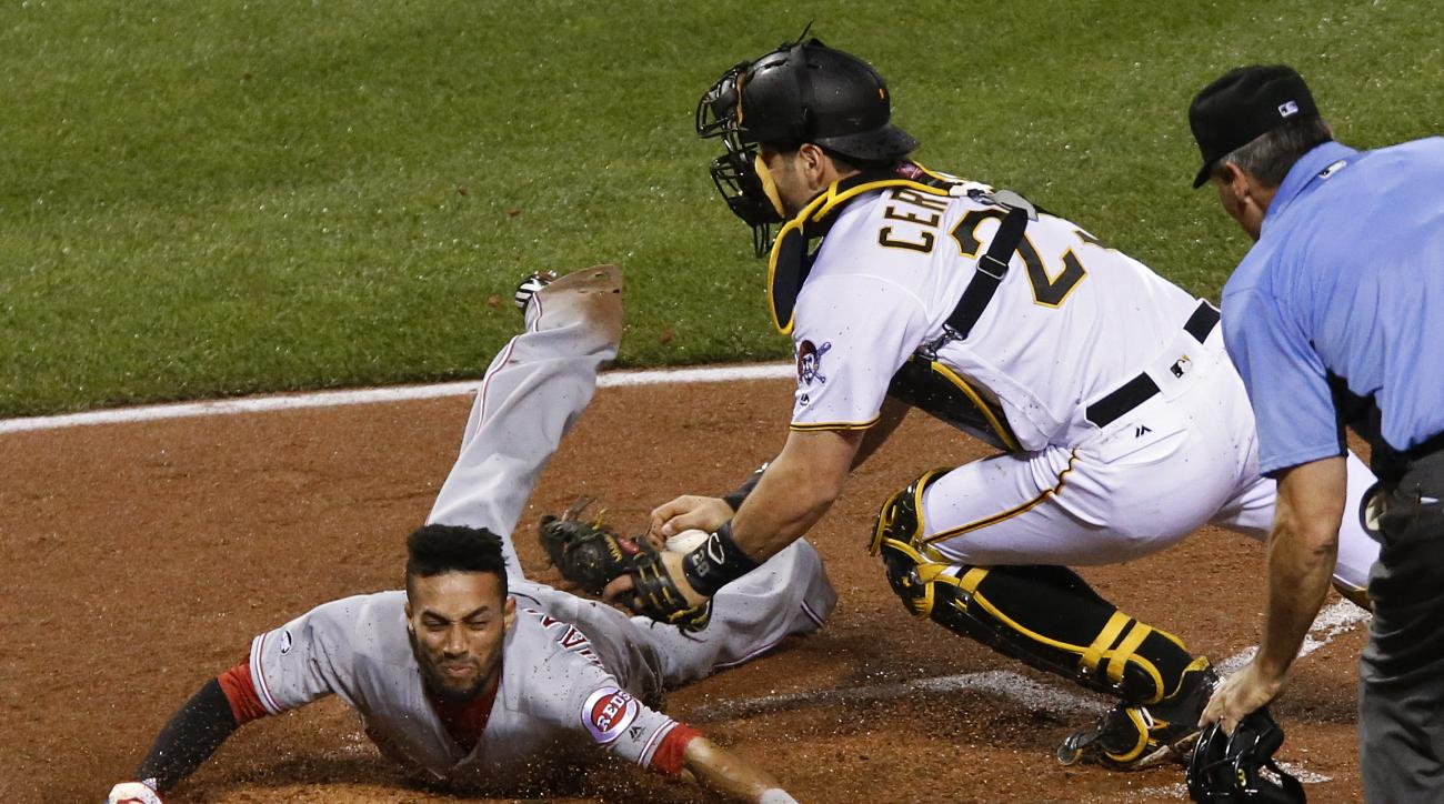 Cincinnati Reds' Billy Hamilton slides under the tag by Pittsburgh Pirates catcher Francisco Cervelli with umpire Angel Hernandez watches during the fifth inning of a baseball game in Pittsburgh, Saturday, April 30, 2016. Hamilton scored on a double by Za