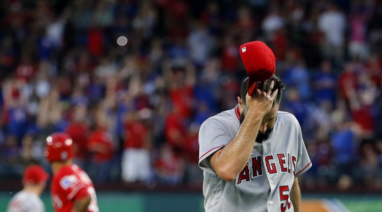 Los Angeles Angels starting pitcher Matt Shoemaker walks off the mound while removing his cap as Texas Rangers' Ian Desmond watches Mitch Moreland three-run home run during the third inning of a baseball game, Saturday, April 30, 2016, in Arlington, Texas