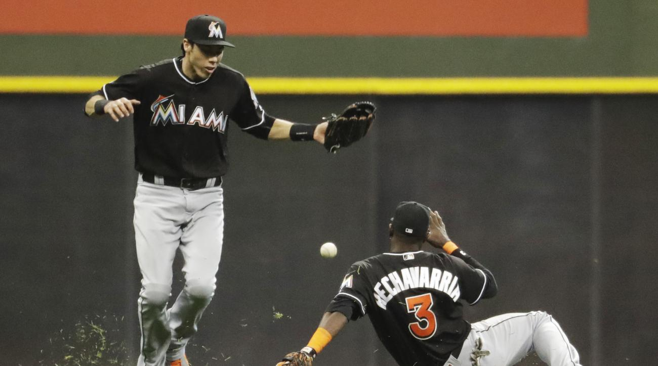 Miami Marlins' Christian Yelich and Adeiny Hechavarria (3) can't catch a two-run single off the bat of Milwaukee Brewers' Ramon Flores during the seventh inning of a baseball game Saturday, April 30, 2016, in Milwaukee. (AP Photo/Morry Gash)
