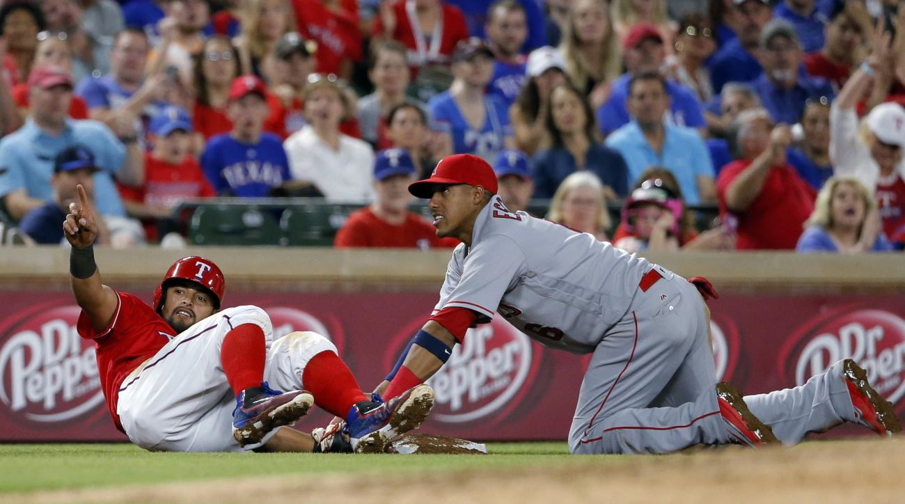 Texas Rangers' Rougned Odor points to the dugout, celebrating after advancing to third on a fly out by Nomar Mazara as Los Angeles Angels' Yunel Escobar looks to the base umpire for the call on a close play during the sixth inning of a baseball game, Satu