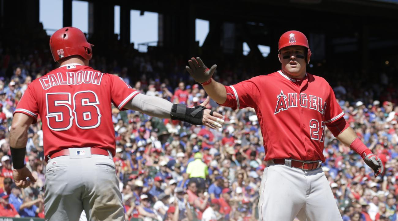 Los Angeles Angels' Kole Calhoun (56) and Mike Trout (27) celebrate after they scored on a single by C.J. Cron against the Texas Rangers during the fifth inning of a baseball game, Sunday, May 1, 2016, in Arlington, Texas. (AP Photo/Jim Cowsert)