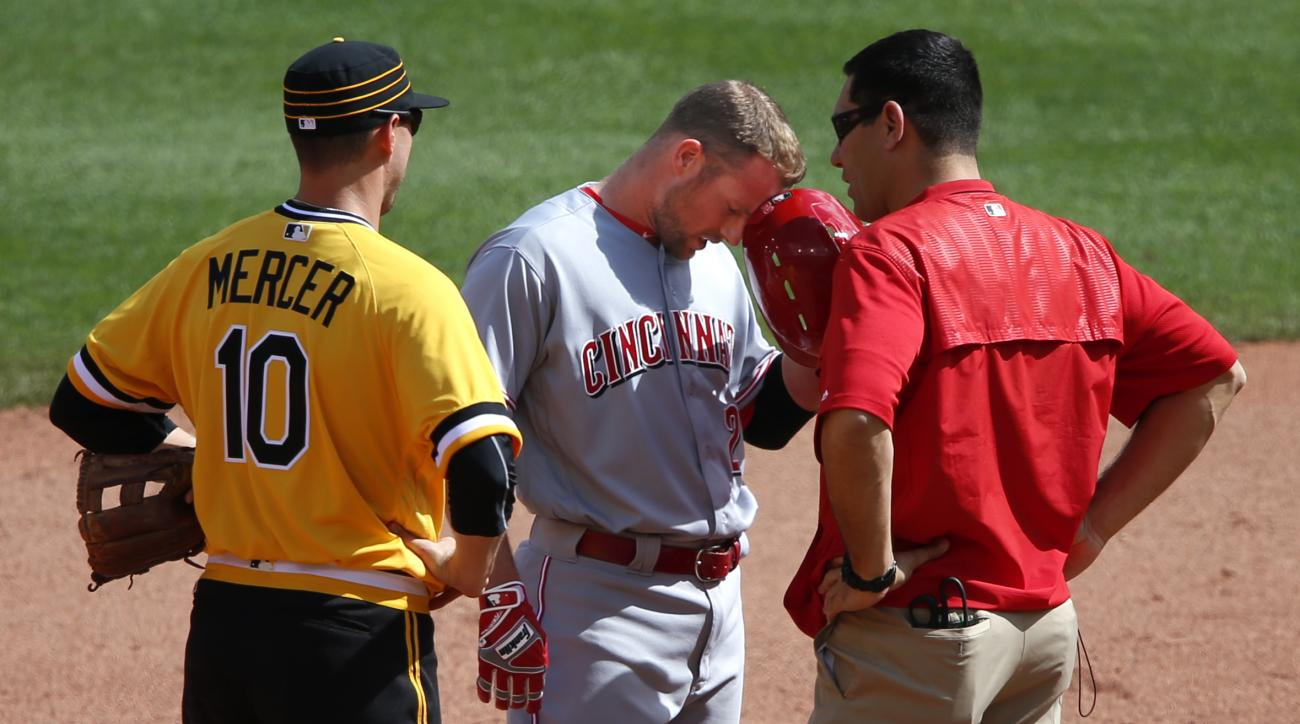 Cincinnati Reds' Zack Cozart, center, is checked by a trainer as Pittsburgh Pirates shortstop Jordy Mercer (10) looks on after being injured on a slide into second during the eighth inning of a baseball game in Pittsburgh, Sunday, May 1, 2016. Cozart left