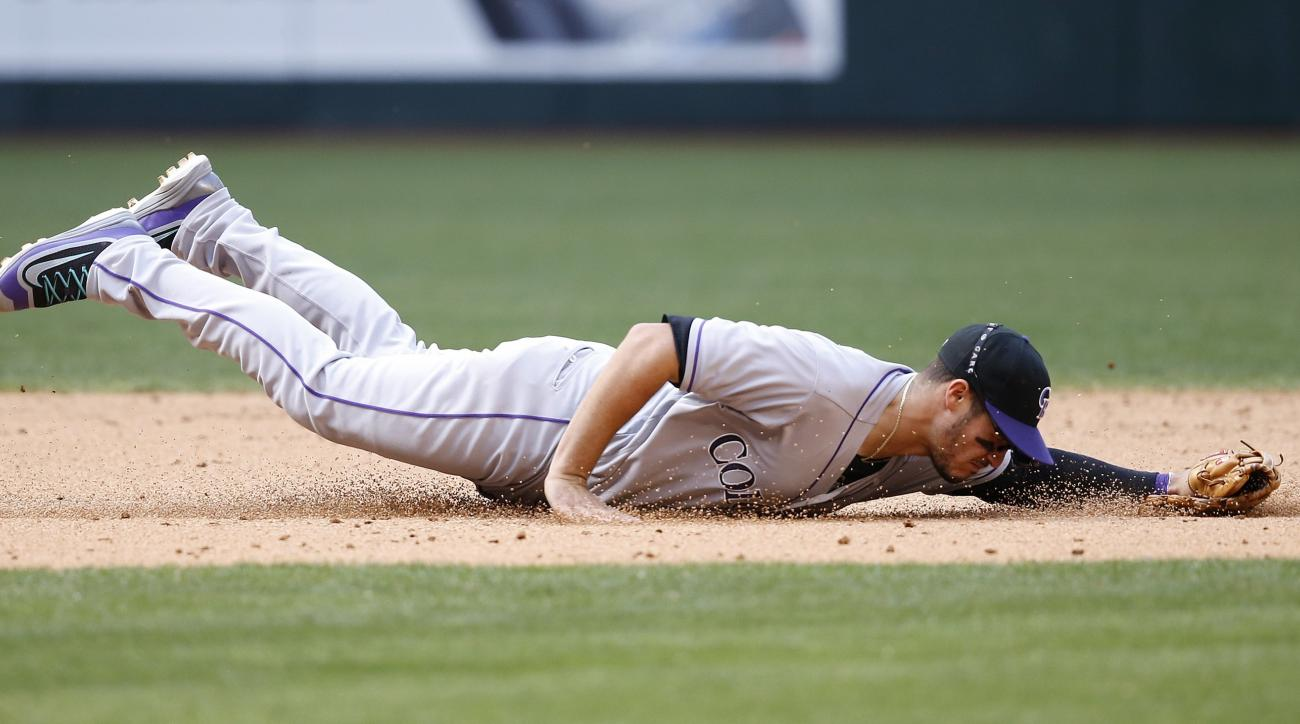 Colorado Rockies' Nolan Arenado dives for but is unable to come up with a ground ball hit by Arizona Diamondbacks' Chris Herrmann during the sixth inning of a baseball game Sunday, May 1, 2016, in Phoenix. (AP Photo/Ross D. Franklin)