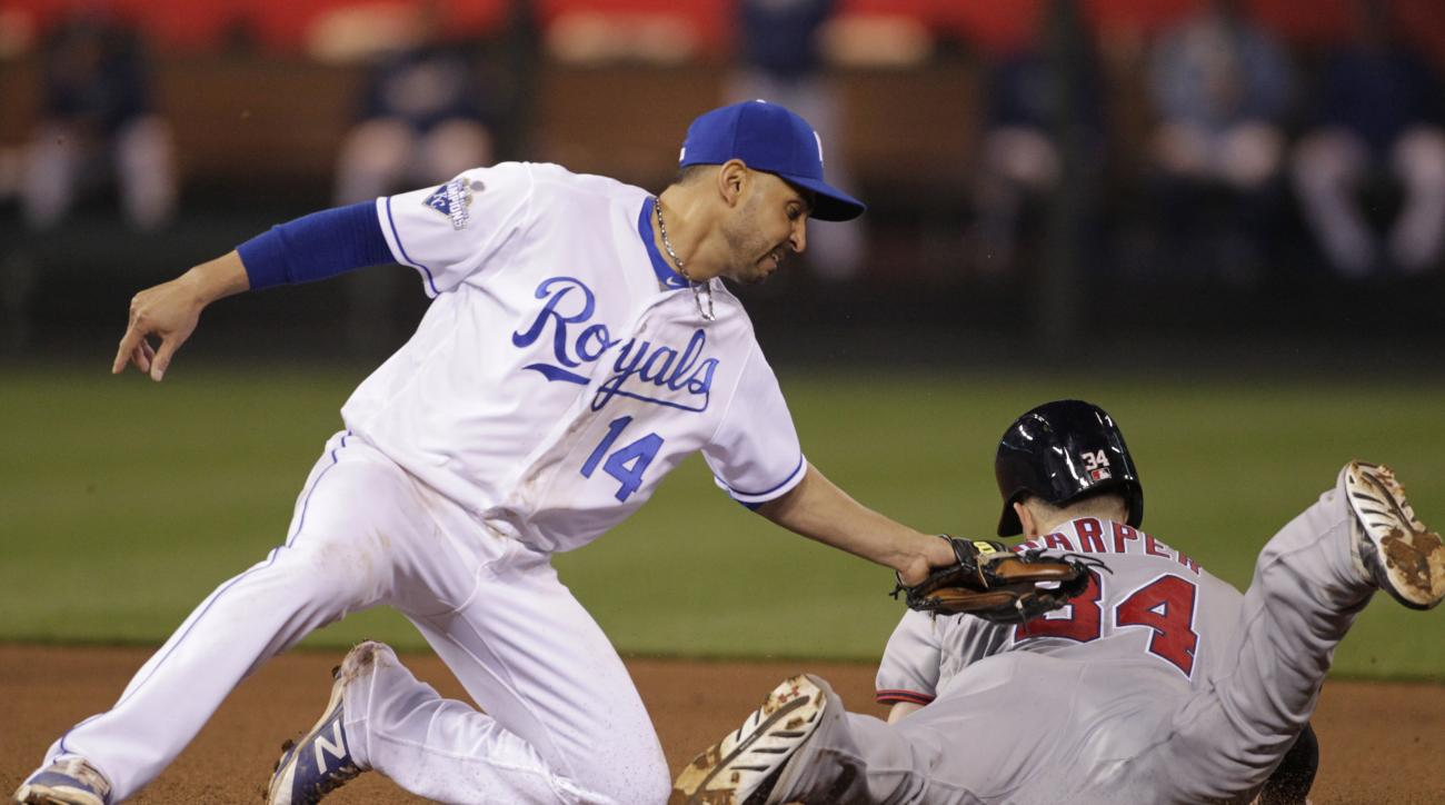 Kansas City Royals second baseman Omar Infante (14) tags out Washington Nationals Bryce Harper (34) as he attempts to steal second base in the sixth inning of a baseball game at Kauffman Stadium in Kansas City, Mo., Monday, May 2, 2016. (AP Photo/Colin E.