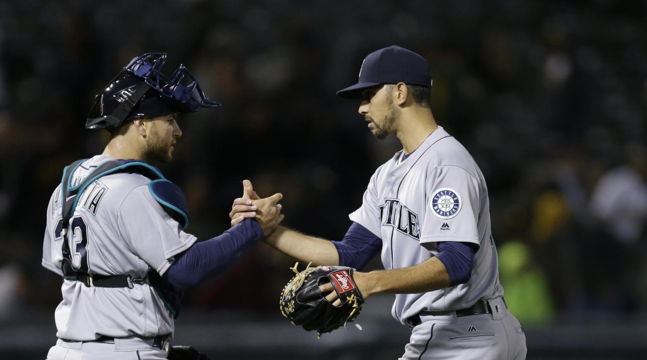 Seattle Mariners pitcher Steve Cishek, right, celebrates the 4-3 defeat of the Oakland Athletics with catcher Chris Iannetta at the end of a baseball game Monday, May 2, 2016, in Oakland, Calif. (AP Photo/Ben Margot)