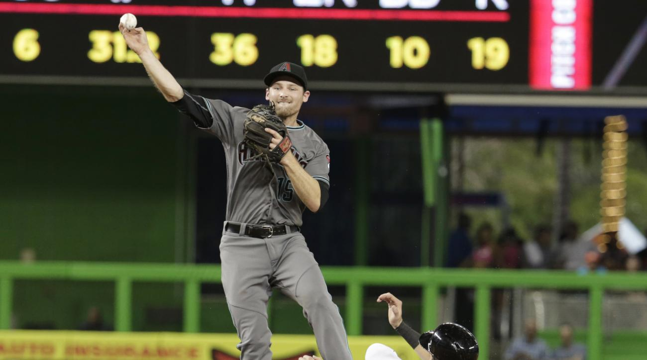 Miami Marlins' Christian Yelich (21) is out at second as Arizona Diamondbacks second baseman Phil Gosselin throws to first during the first inning of a baseball game, Tuesday, May 3, 2016, in Miami. (AP Photo/Lynne Sladky)