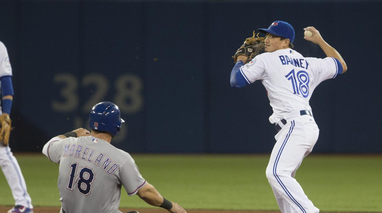 Toronto Blue Jays Darwin Barney (18) throws to first as he outs Texas Rangers Mitch Moreland (18) at second during the seventh inning of a baseball game, Tuesday, May 3, 2016 in Toronto.  (Chris Young/The Canadian Press via AP) MANDATORY CREDIT