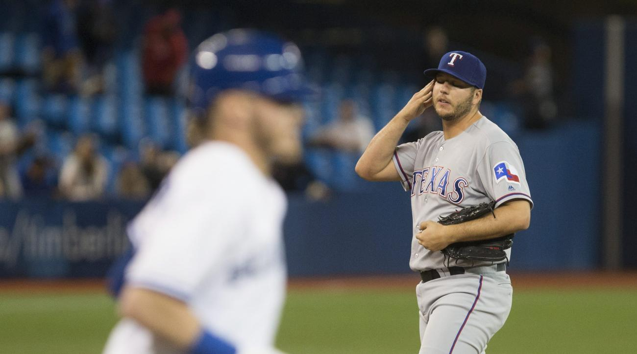 Texas Rangers pitcher Shawn Tolleson, right, looks on as he walks Toronto Blue Jays Josh Donaldson, left, to load the bases during ninth inning of a baseball game, Tuesday, May 3, 2016, in Toronto. (Chris Young/The Canadian Press via AP) MANDATORY CREDIT