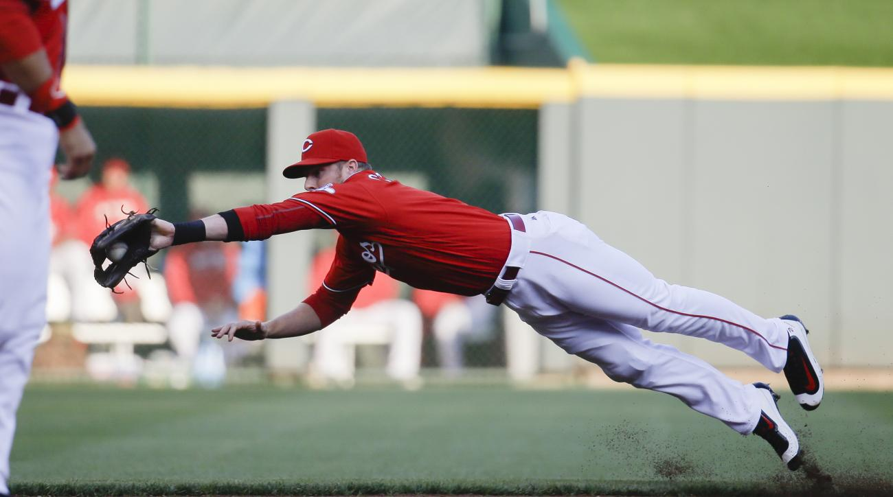 Cincinnati Reds shortstop Zack Cozart dives to catch out Milwaukee Brewers' Alex Presley in the first inning of a baseball game, Thursday, May 5, 2016, in Cincinnati. (AP Photo/John Minchillo)
