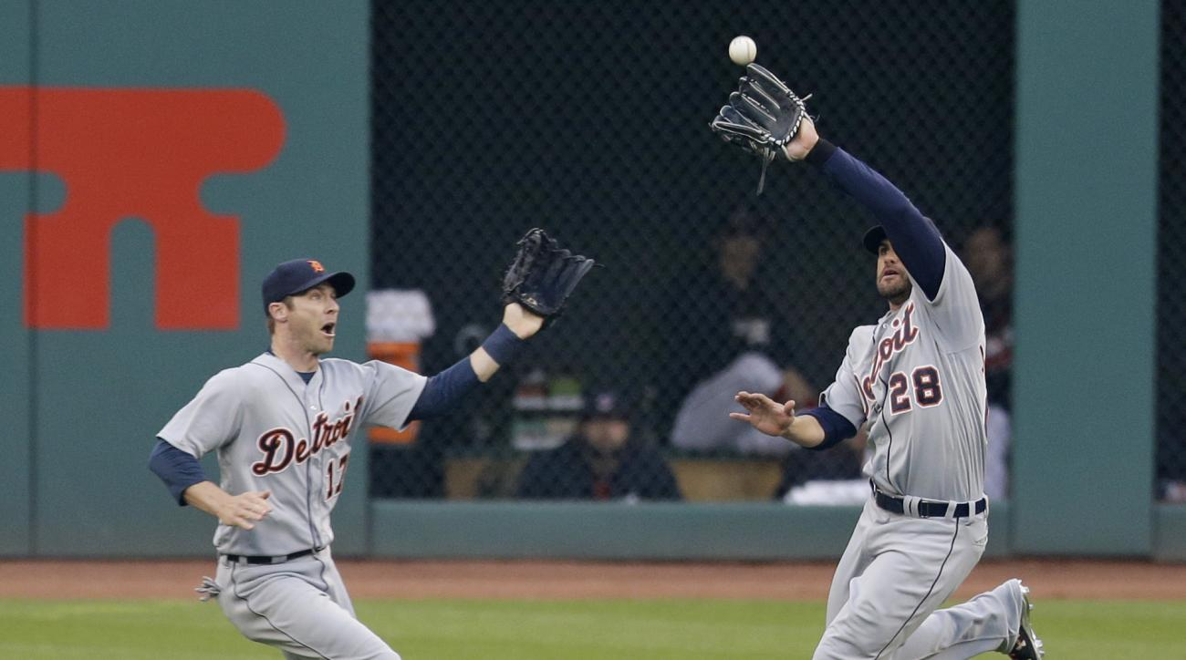 Detroit Tigers' J.D. Martinez, right, catches a ball hit by Cleveland Indians' Juan Uribe in the fifth inning of a baseball game, Thursday, May 5, 2016, in Cleveland. Andrew Romine, left, watches. Uribe was out on the play. (AP Photo/Tony Dejak)