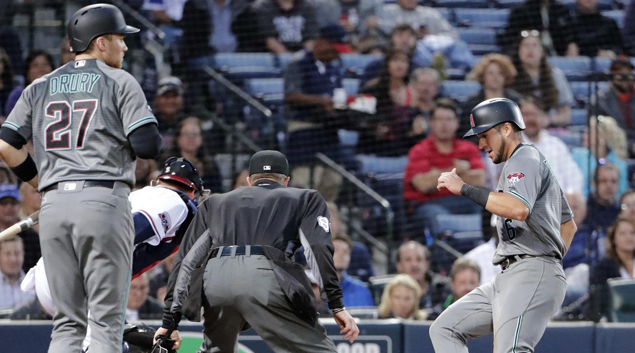 Arizona Diamondbacks' David Peralta, right, scores on a fielding error as Atlanta Braves catcher A.J. Pierzynski, rear, chases the ball in the third inning of a baseball game Friday, May 6, 2016, in Atlanta. (AP Photo/David Goldman)