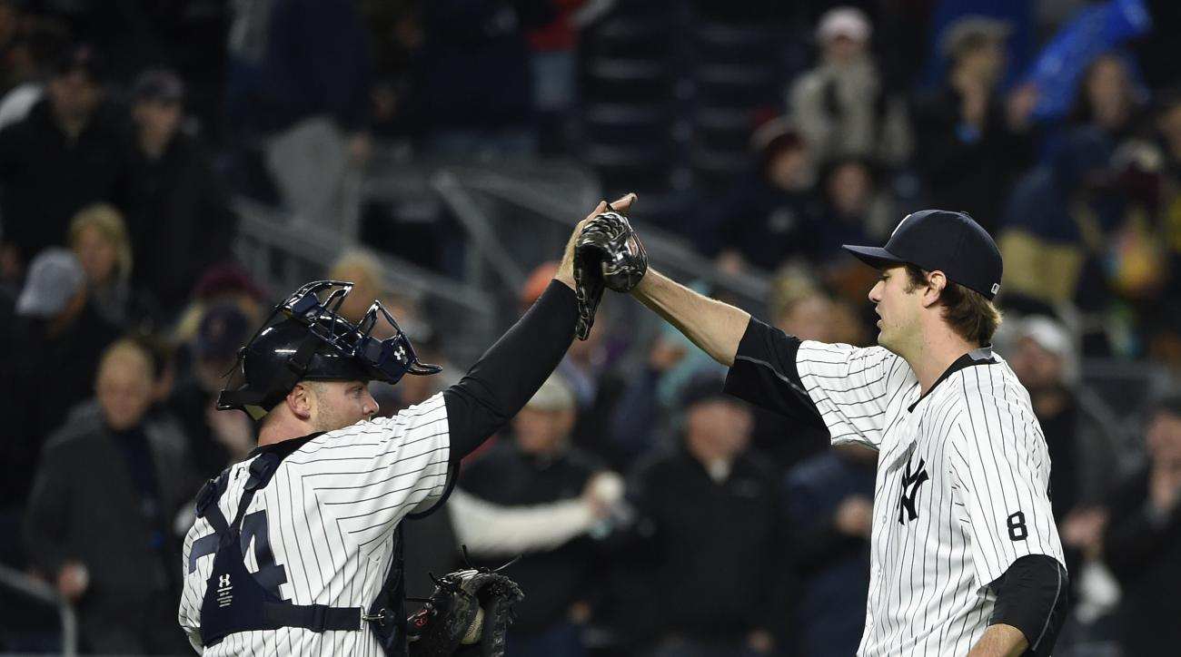 New York Yankees catcher Brian McCann (34) congratulates relief pitcher Andrew Miller after they defeated the Boston Red Sox in a baseball game, Friday, May 6, 2016, in New York. (AP Photo/Kathy Kmonicek)