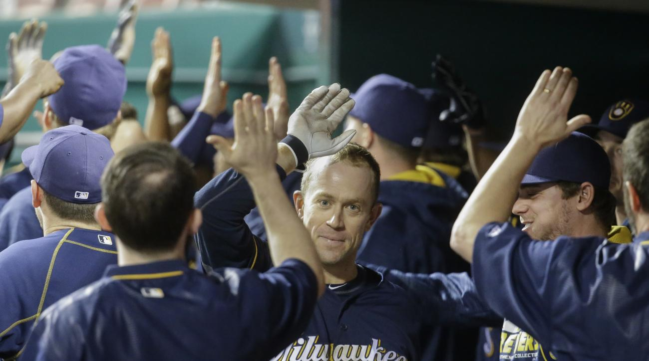 Milwaukee Brewers' Aaron Hill (9) celebrates in the dugout after hitting a go-ahead grand slam in the tenth inning of a baseball game against the Cincinnati Reds, Saturday, May 7, 2016, in Cincinnati. (AP Photo/John Minchillo)