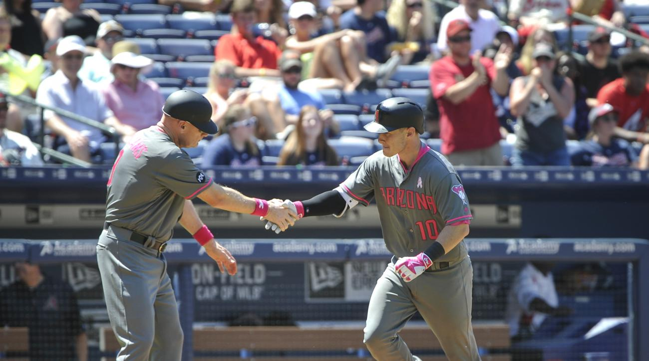 Arizona Diamondbacks' Chris Herrmann (10) rounds third base as third base coach Matt Williams congratulates him on his home run during the seventh inning of a baseball game against the Atlanta Braves, Sunday, May 8, 2016, in Atlanta. (AP Photo/John Amis)