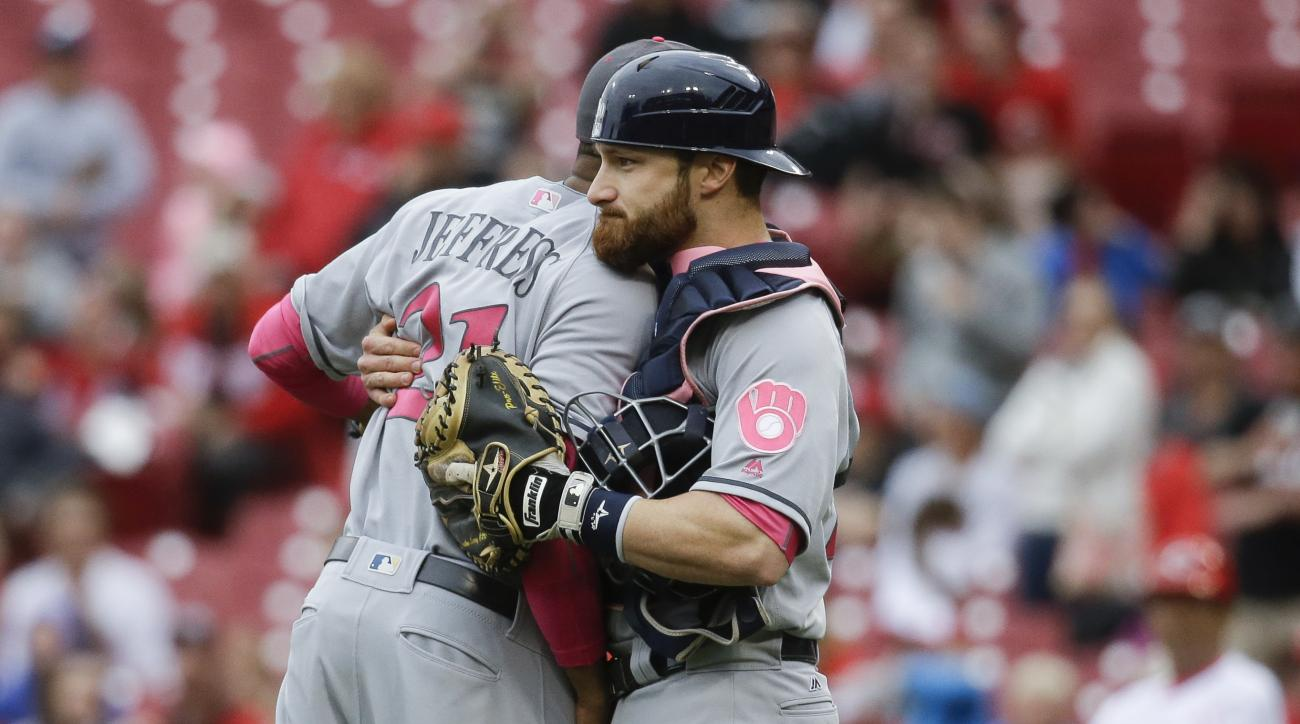 Milwaukee Brewers relief pitcher Jeremy Jeffress (21) and catcher Jonathan Lucroy, right, celebrate after a baseball game against the Cincinnati Reds, Sunday, May 8, 2016, in Cincinnati. (AP Photo/John Minchillo)