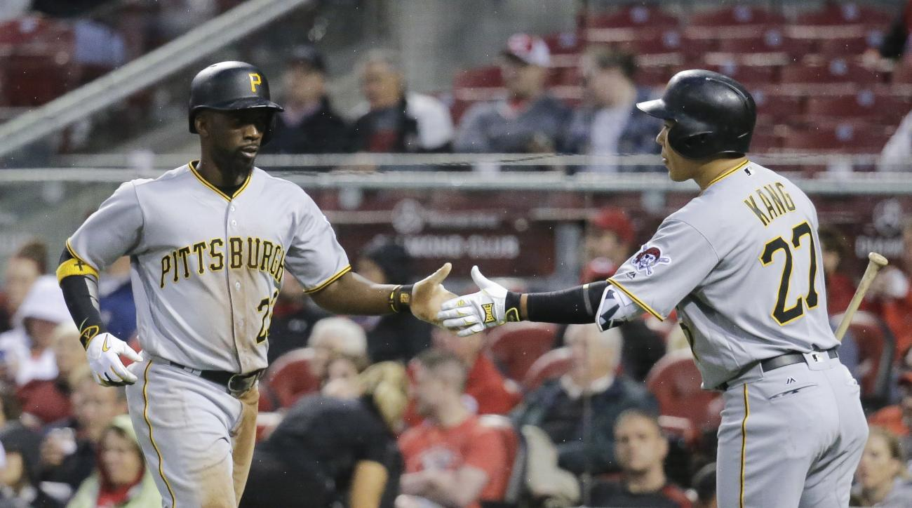 Pittsburgh Pirates' Andrew McCutchen (22) celebrates with Jung Ho Kang (27) after scoring on a sacrifice fly by Francisco Cervelli in the sixth inning of a baseball game, Monday, May 9, 2016, in Cincinnati. (AP Photo/John Minchillo)