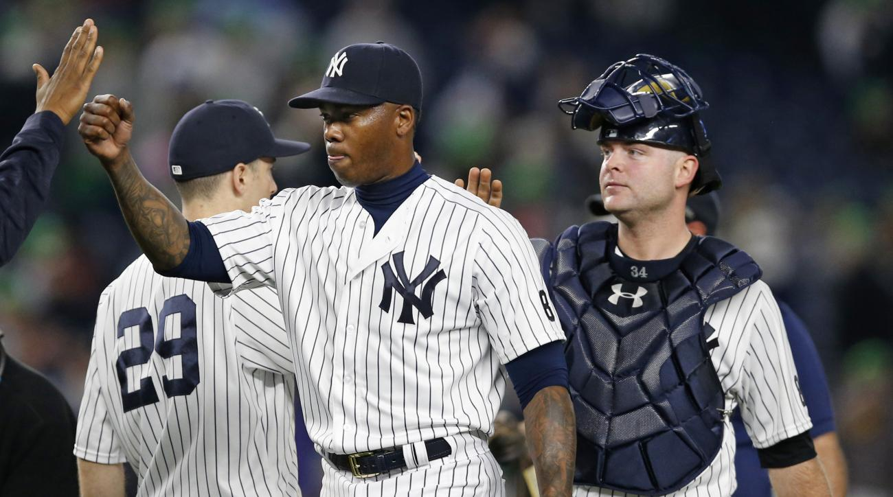 Teammates congratulate New York Yankees relief pitcher Aroldis Chapman, center, after Chapman, the first player disciplined under Major League Baseball's new domestic violence policy, closed out the Yankees 6-2 victory in a baseball game against the Kansa