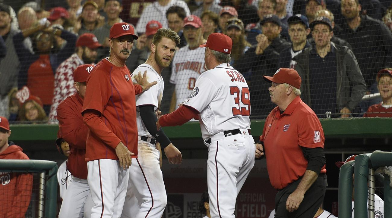 Washington Nationals' Bryce Harper, center, is restrained by pitching coach Mike Maddux, left, and hitting coach Rick Schu (39) after Harper was ejected in the dugout during the ninth inning of an interleague baseball game against the Detroit Tigers, Mond
